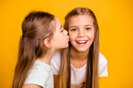 Foto de Close-up portrait of two nice cool attractive lovely sweet cheerful cheery positive girlish girls having fun kissing care isolated over bright vivid shine yellow background - Imagen libre de derechos