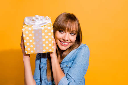 Foto de Close up portrait of attractive beautiful she her lady holding large giftbox in hands glad ready to unpack it wearing casual jeans denim shirt clothes isolated on yellow background - Imagen libre de derechos