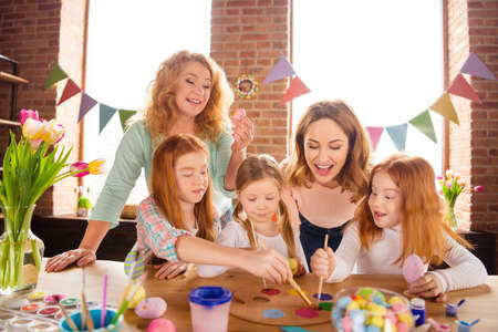Photo pour Portrait of nice charming attractive lovely cheerful ladies helping girls making decor cool stylish things on table for event gift wow present decoration in house brick loft industrial interior room - image libre de droit