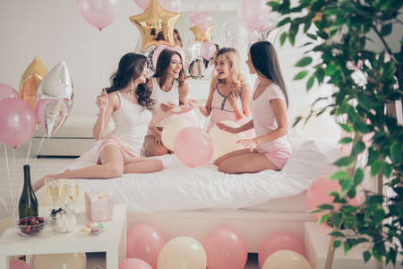 Close up photo beautiful she her fancy pretty cute chic ladies on white bed linen sheets bright decorated room discuss boyfriends sharing gossip rumors excited sleep costumes girls day night
