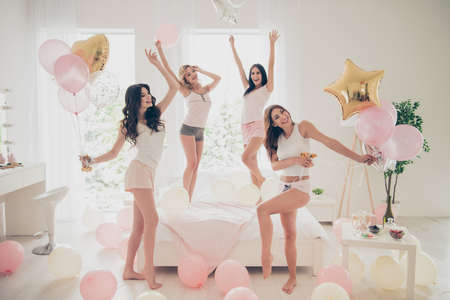 Foto de Close up photo beautiful she her fancy pretty cute classy ladies white bed linen sheets bright room balloons festive dancing queens sleep costumes girls day night holiday gathering theme party indoors - Imagen libre de derechos