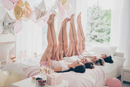 Foto de Profile side view of nice lovely attractive adorable slender fit thin slim figure girlfriends having fun lying on bed raising smooth healthy legs up in light white interior decorated house - Imagen libre de derechos