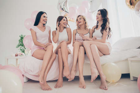 Foto de Portrait of nice attractive lovely fit thin slim well-groomed cheerful girlfriends having fun sitting on bed barefoot vacation in light white interior decorated house indoors - Imagen libre de derechos