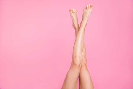 Foto de Cropped close-up image view photo of nice perfect long attractive feminine fit thin slim soft smooth shine shaven legs ad advert isolated over pink pastel background - Imagen libre de derechos