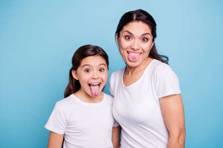 Foto de Close up photo beautiful two people brown haired mom little daughter friends hipsters silly mouth opened tongue out fooling around playing wear white t-shirts isolated bright blue background - Imagen libre de derechos