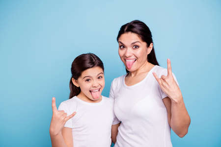 Foto de Close up photo beautiful two people brown haired mom little daughter friends hipsters mouth opened tongue out rock music lovers amazed wear white t-shirts isolated bright blue background - Imagen libre de derechos