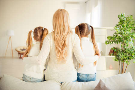 Photo pour Rear back behind view of nice adorable blonde stylish trendy slim people kind tender mom mommy mum girls sitting hugging in modern light white interior room indoors - image libre de droit