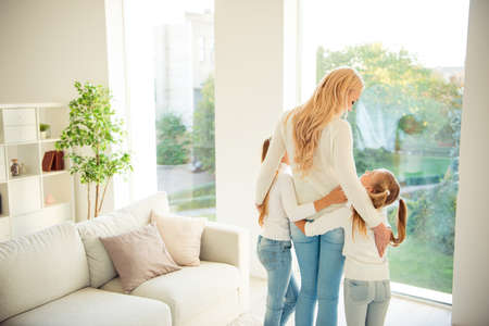 Photo pour Rear back behind view of nice stylish trendy slim people kind tender mom mommy mum girls hugging in front of window in modern light white interior room indoors - image libre de droit