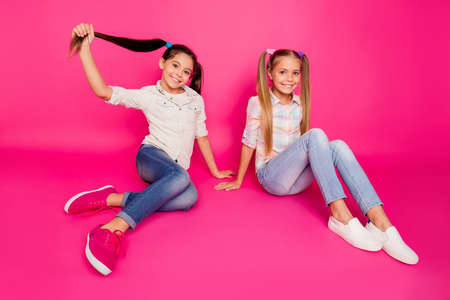 Foto de Close up photo two little age she her girls leaning hands arms best friends sit floor optimistic smile winners wearing casual jeans denim checkered plaid shirts isolated rose vibrant vivid background - Imagen libre de derechos