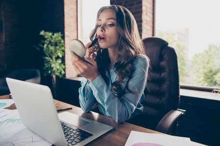 Photo pour Close up photo beautiful she her business lady get ready skype tell speak conversation use lipstick to refresh everyday visage sit office big large comfort chair wearing formal wear suit - image libre de droit
