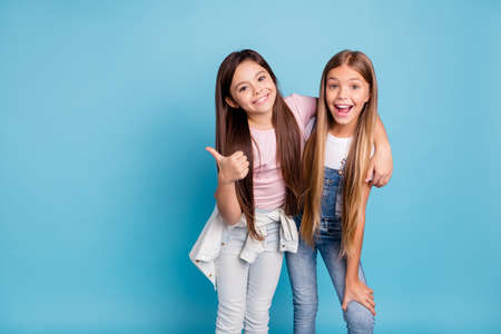 Foto de Portrait of two people nice cute lovely charming dreamy attractive cheerful straight-haired pre-teen girls siblings showing aside ad promotion copy space isolated on blue turquoise background - Imagen libre de derechos