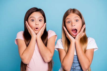 Close-up portrait of two people nice cute attractive charming scared toothy straight-haired pre-teen girls showing omg expression scary news isolated over blue pastel background