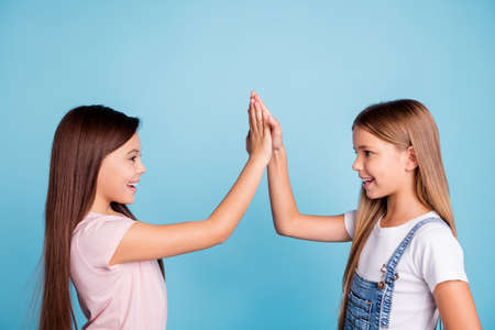 Foto de Profile side view portrait of nice-looking cute lovely sweet friendly attractive cheerful straight-haired girls standing clapping palms good decision choice siblings isolated over blue pastel background - Imagen libre de derechos