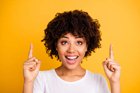 Foto de Close-up portrait of her she nice lovely adorable attractive cheerful wavy-haired girl pointing two fingers up isolated on bright vivid shine yellow background - Imagen libre de derechos
