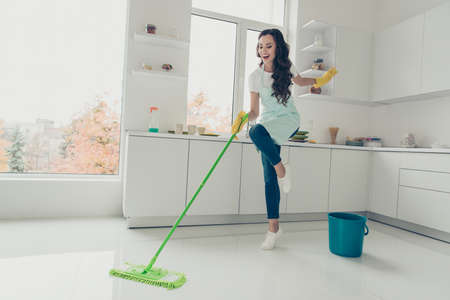 Photo pour Full length body size side profile photo beautiful cheerful hardworking duties she her lady house love clean dancing singing wear jeans denim casual t-shirt covered cute apron bright light kitchen - image libre de droit