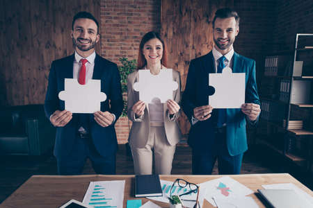 Photo pour Portrait of three nice chic classy elegant stylish cheerful executive managers holding in hands showing big large puzzle in loft industrial interior workplace workstation - image libre de droit