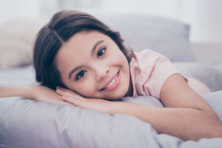 Photo for Close up photo cute sweet beautiful she her little girl lying down on pillow hands arms hold head homey sunday mood wear home t-shirt pants comfortable apartments flat bright light colored room - Royalty Free Image
