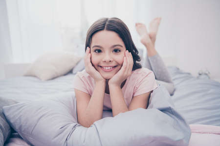 Foto de Close up photo beautiful she her little girl curly wavy lying down pillow hands arms hold head homey sunday mood wear home t-shirt pants comfortable apartments flat bright light colored room - Imagen libre de derechos