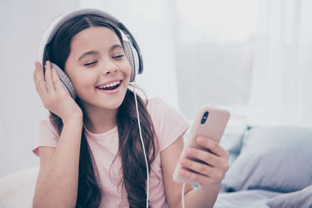 Foto per Close up photo beautiful she her little girl smart phone hands earflaps eyes closed learn text new popular song curly wavy wear home t-shirt pants comfortable apartments flat bright light colored room - Immagine Royalty Free