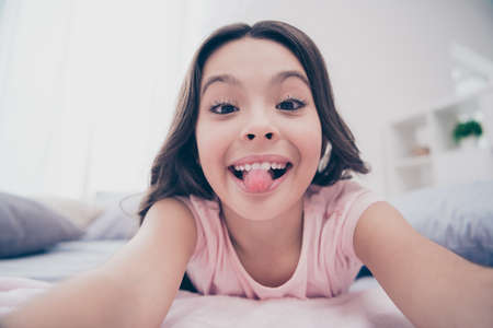 Photo pour Close up photo cute beautiful she her little girl lying down linen sheets homey sunday make take selfies tongue out mouth wear home t-shirt pants comfortable apartments flat bright light colored room - image libre de droit