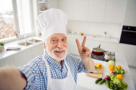 Photo pour Close up photo cheer grey haired he his him grandpa telephone make take selfies video followers show v-sign say hi wear baker chefs costume casual checkered plaid shirt outfit house kitchen - image libre de droit
