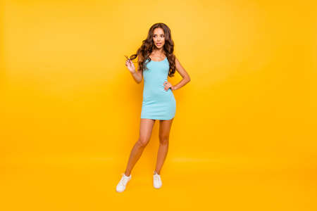 Foto per Full length body size photo beautiful her she lady hands arms hold one curl look side empty space slim ideal shape fit wearing blue teal green everyday short dress clothes isolated yellow background - Immagine Royalty Free