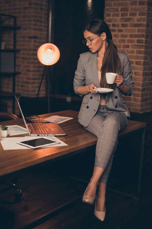 Photo pour Vertical close up photo attentive she her business lady chief checking look notebook hold hot beverage information learn study compare analyze sit office table wear specs formal wear checkered suit - image libre de droit
