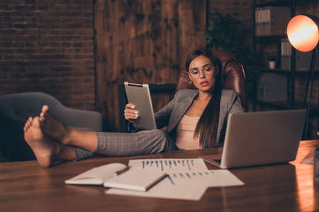 Foto de Close up side profile photo she her business lady chief hard week look e-reader e-book report information learn study compare analyze legs table sit office chair wear specs formal wear checkered suit - Imagen libre de derechos