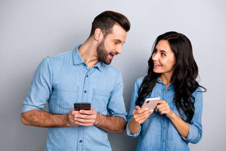 Photo pour Close up photo wondered she her he him his lady guy telephone smart phone hands arms read reader news look interest eyes wear casual jeans denim shirts outfit clothes isolated light grey background - image libre de droit