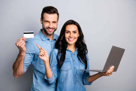 Foto de Close up photo beautiful amazing she her he him his couple lady guy hold credit card notebook show simple way internet buy pay  wear casual jeans denim shirts outfit clothes isolated grey background - Imagen libre de derechos