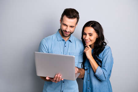 Foto de Portrait of charming inspired students using electronic devices watching videos browsing sites social networks isolated dressed in blue denim clothing on gray background - Imagen libre de derechos