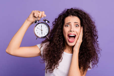 Foto de Close-up portrait of her she nice cute charming attractive crazy mad devastated brunette wavy-haired lady showing clock hurry oops isolated on bright vivid shine violet purple background - Imagen libre de derechos