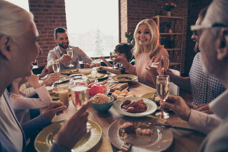 Photo for Close up photo big family birthday toast raise wineglasses golden beverage members brother sister granny mom dad grandpa little son daughter sit round festive holiday dishes table loft house indoors - Royalty Free Image