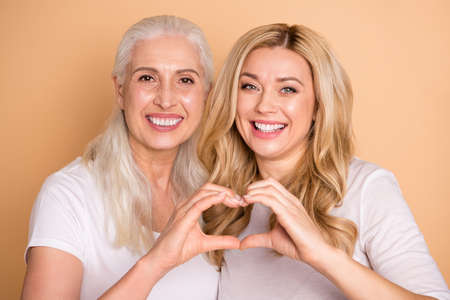 Photo pour Close-up portrait of nice-looking winsome lovely attractive sweet charming cute cheerful cheery ladies wearing white t-shirt showing romance heart sign isolated over beige pastel background - image libre de droit