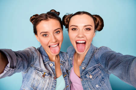 Foto de Close up photo of carefree childish cheerful teenage ladies making photos faces blogging isolated on free time enjoying dressed in denim jackets on pastel background - Imagen libre de derechos