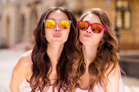 Photo for Close up photo gorgeous attractive millennial people coquettish attract boys men love lovers travel students send air kisses romance romantic long hair modern bright specs pastel outfit town center. - Royalty Free Image