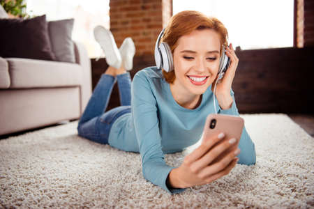 Photo pour Close up photo beautiful she her lady hands smart phone earflaps read words signing favorite songs wear blue pullover jeans denim clothes lying floor fluffy carpet divan house loft living room indoors - image libre de droit
