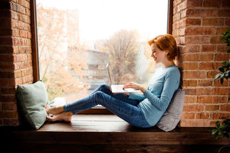 Photo pour Close up side profile photo beautiful she her lady hands texting notebook foreign friends excited wear blue pullover jeans denim clothes sit comfy big large windowsill house loft living room indoors - image libre de droit