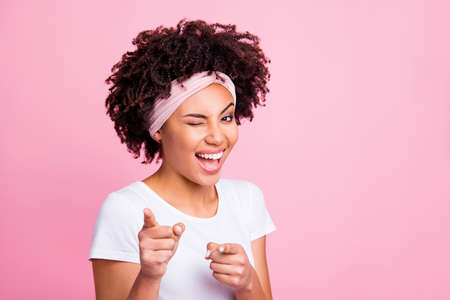 Photo pour Close up photo beautiful amazing funny she her dark skin winking eyes positive friendly indicating fingers your turn its you symbol wear head scarf casual white t-shirt isolated pink bright background - image libre de droit