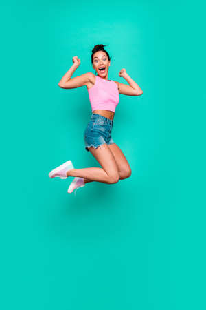Foto de Vertical full length side profile body size photo beautiful she her funny yelling trendy hairdo jump high lucky lottery wear casual pink tank-top jeans denim shorts isolated teal turquoise background - Imagen libre de derechos