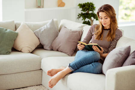 Foto de Portrait of her she nice-looking cute charming lonely attractive wavy-haired girl sitting on divan alone reading poems in light white interior room - Imagen libre de derechos