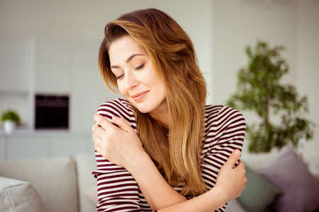 Photo pour Close up photo charming nice lady youth hug her self she hands close yes feel glad enjoy pleasant have holidays vacations striped shirt modern outfit have long curly wavy hair sit divan living room - image libre de droit