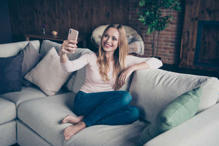 Photo portrait of attractive cheerful calm positive optimistic charming she her lady using telephone having blog sitting on divan without shoes