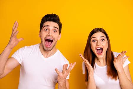Photo pour Close up photo funky amazing she her he him his couple hands arms raised air yell unbelievable luck lucky cheerleader football match wear casual white t-shirts outfit isolated yellow background - image libre de droit