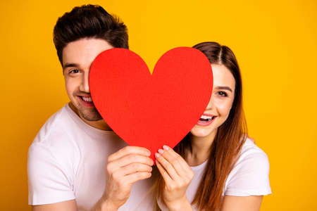 Foto de Close up photo beautiful she her he him his guy lady hiding facial expression laugh laughter hold hands arms heart shape paper postcard in love wear casual white t-shirts isolated yellow background - Imagen libre de derechos