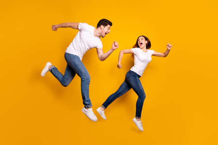 Photo pour Full length side profile body size photo funky she her he him his pair jumping high hurry shopping raised fists yell scream shout loud wear casual jeans denim white t-shirts isolated yellow background - image libre de droit