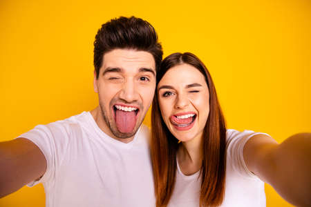 Photo for Self-portrait of his he her she two nice attractive cheerful cheery childish comic playful people husband wife showing tongue out having fun isolated over vivid shine bright yellow background - Royalty Free Image