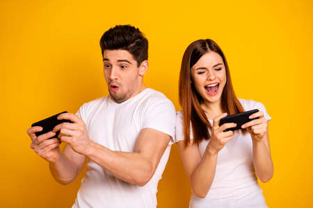Foto de Portrait of his he her she two nice attractive stylish trendy cheerful cheery childish positive people playing app 5g battle contest isolated over vivid shine bright yellow background - Imagen libre de derechos
