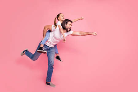 Foto de Full length side profile body size photo she her little lady he him his daddy dad hold little princess piggyback hands arms ready fly wear casual white t-shirts denim jeans isolated pink background - Imagen libre de derechos