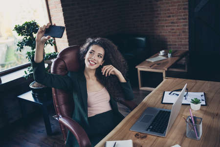 Portrait of positive cheerful satisfied freelancer entrepreneur leisure true blogger blog make photos sit chair armchair have table feel content wear classic outfit indoors interior